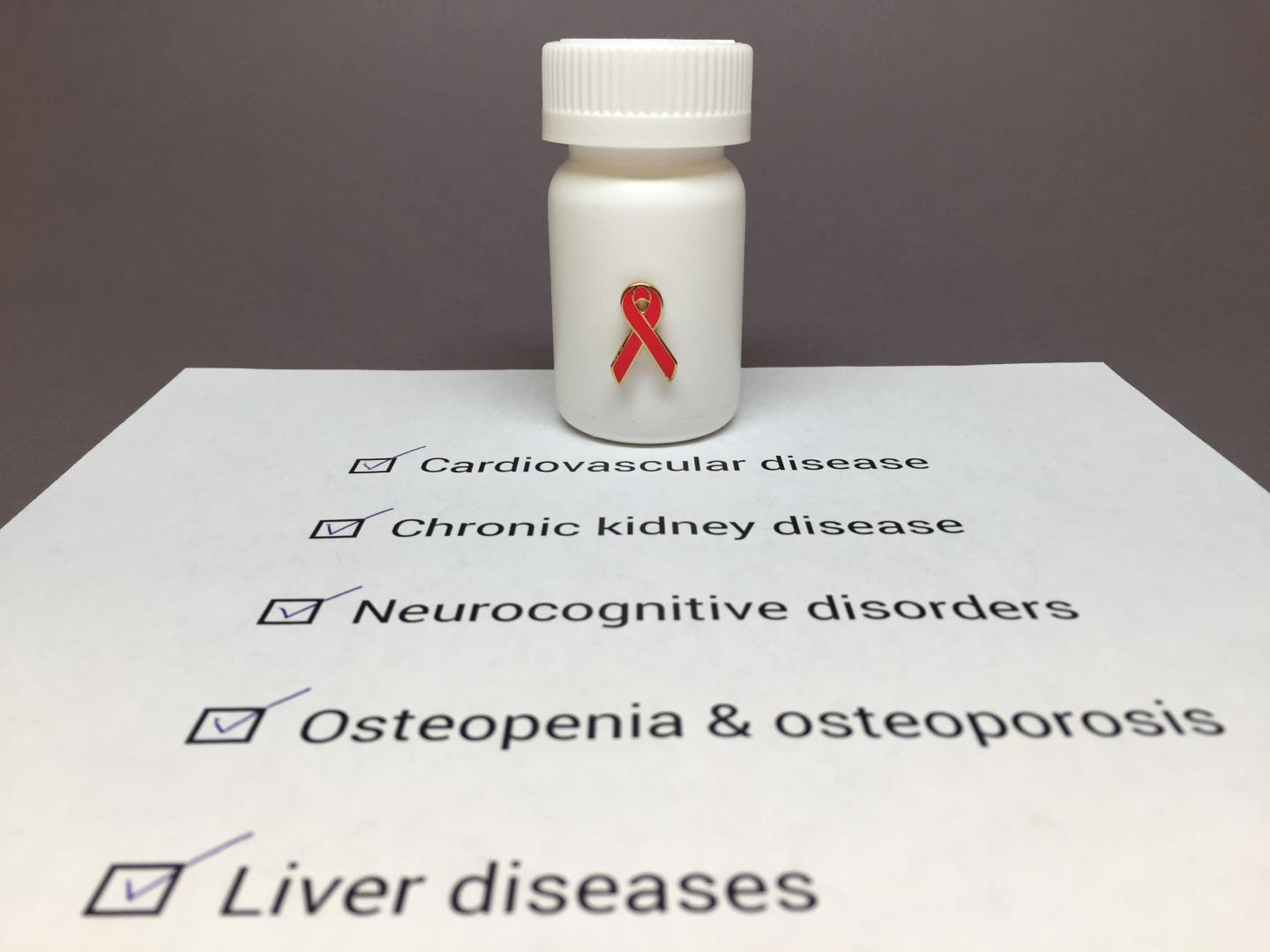 Pill Bottle with a Red HIV Awareness Ribbon Sitting on a Piece of Paper Listing of HIV Comorbidities