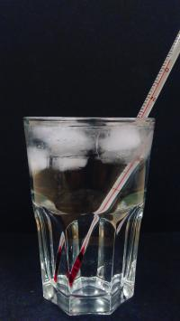 A Glass of Ice Water with a Thermometer Measuring 4 Degrees C at the Bottom