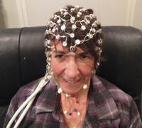 An Adult with EEG Sensors to Record the Brain's Response to Sound