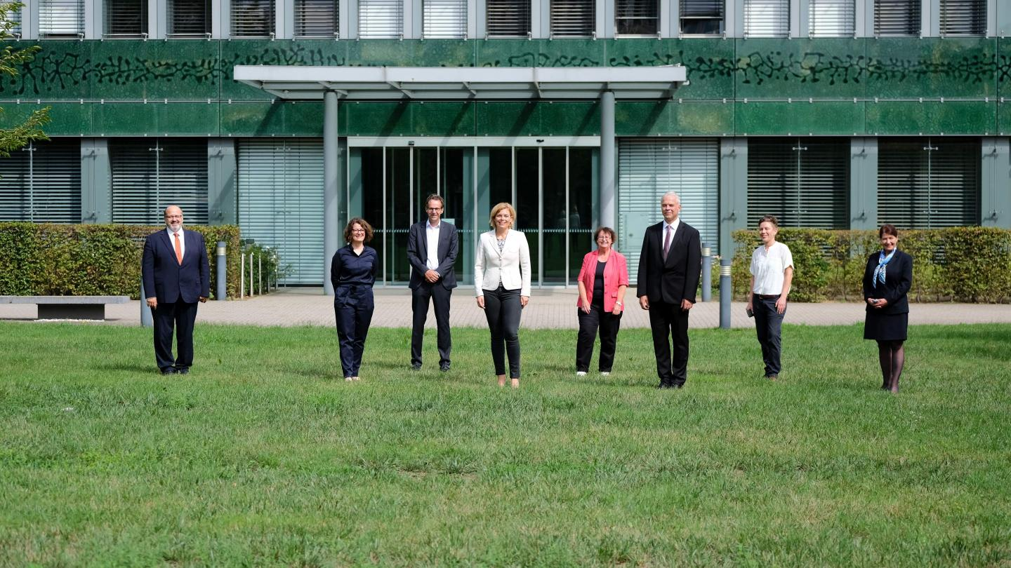 Eight People In Business Clothes On Some Grass In Front Of A Building