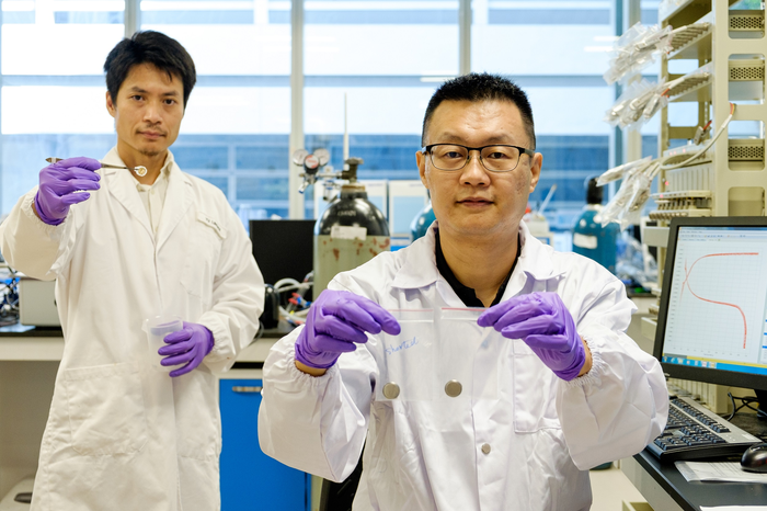 Prof Jason Xu (right) holding a short-circuited battery in his right hand and the new technology in his left