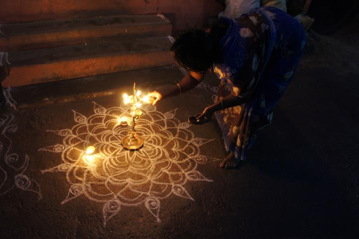 A Woman Lights An Oil Lamp to Celebrate the Hindu Festival of Lights