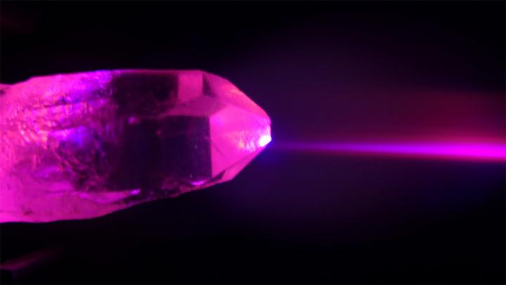 single, brightly lit crystal on black background
