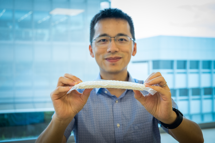 NTU Asst Prof Wang Yifan holding the stiffened nylon chain mail in a vacuum-packed envelope