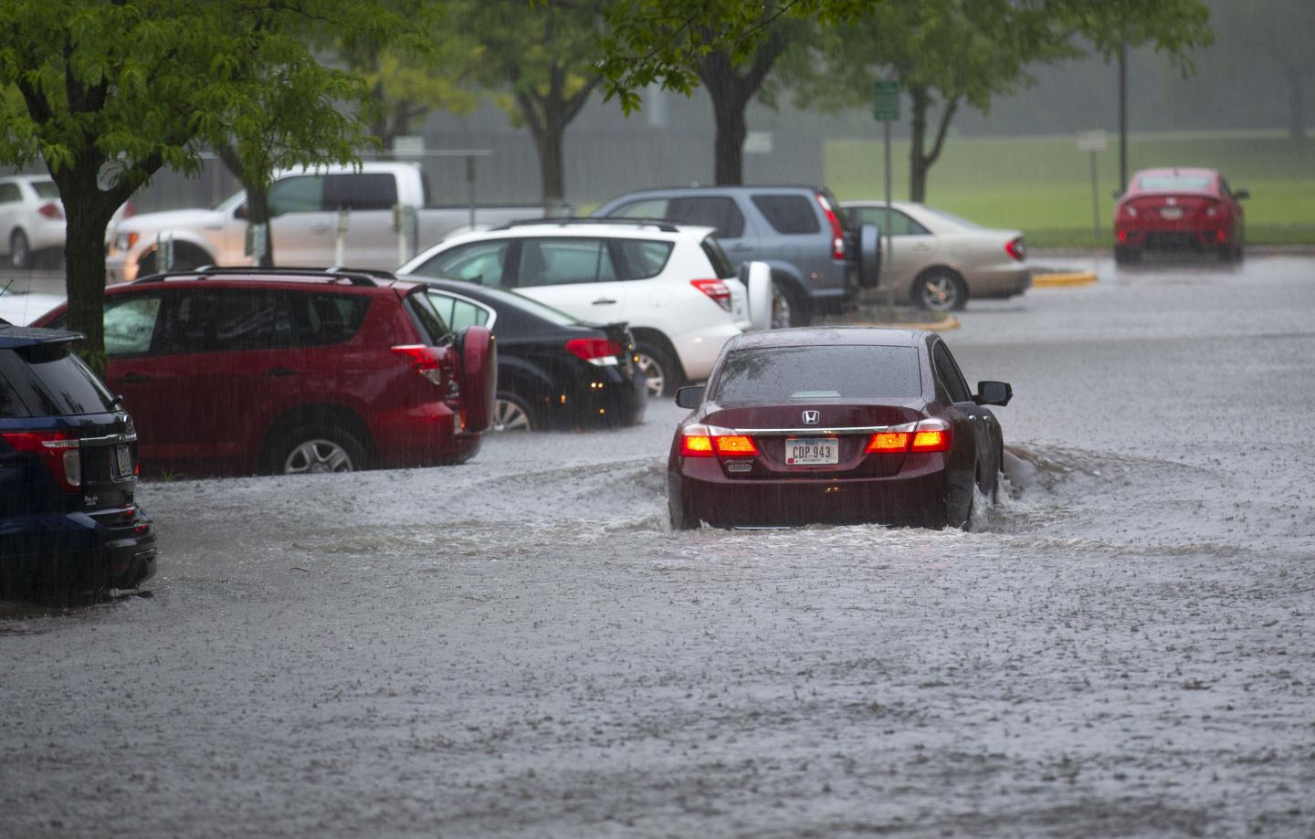 Car Driving through Flooded Parking Lot