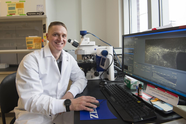 Vanderheyden examining sleep-promoting cells w fluorescent microscopy