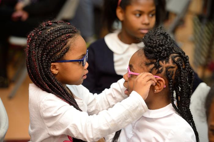 School children trying on new eyeglasses