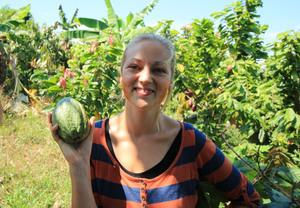 female researcher holding green, oval cocoa pod, standing in landscape