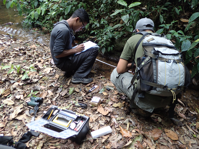 Martim Murillo measures water quality of Rio Jacagua, assisted by Farlem Espana.