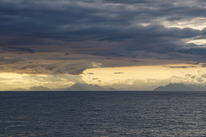 Dramatic clouds and Alaska's southern coastline frame the Gulf of Alaska during a scientific cruise in summer 2017.